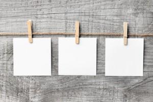 Drei Notizzettel vor Holzhintergrund